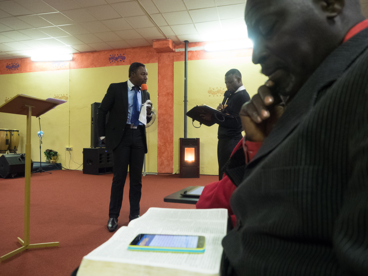 During the sermon, Maxwell Adjei follow it reading the Bible on his iPhone