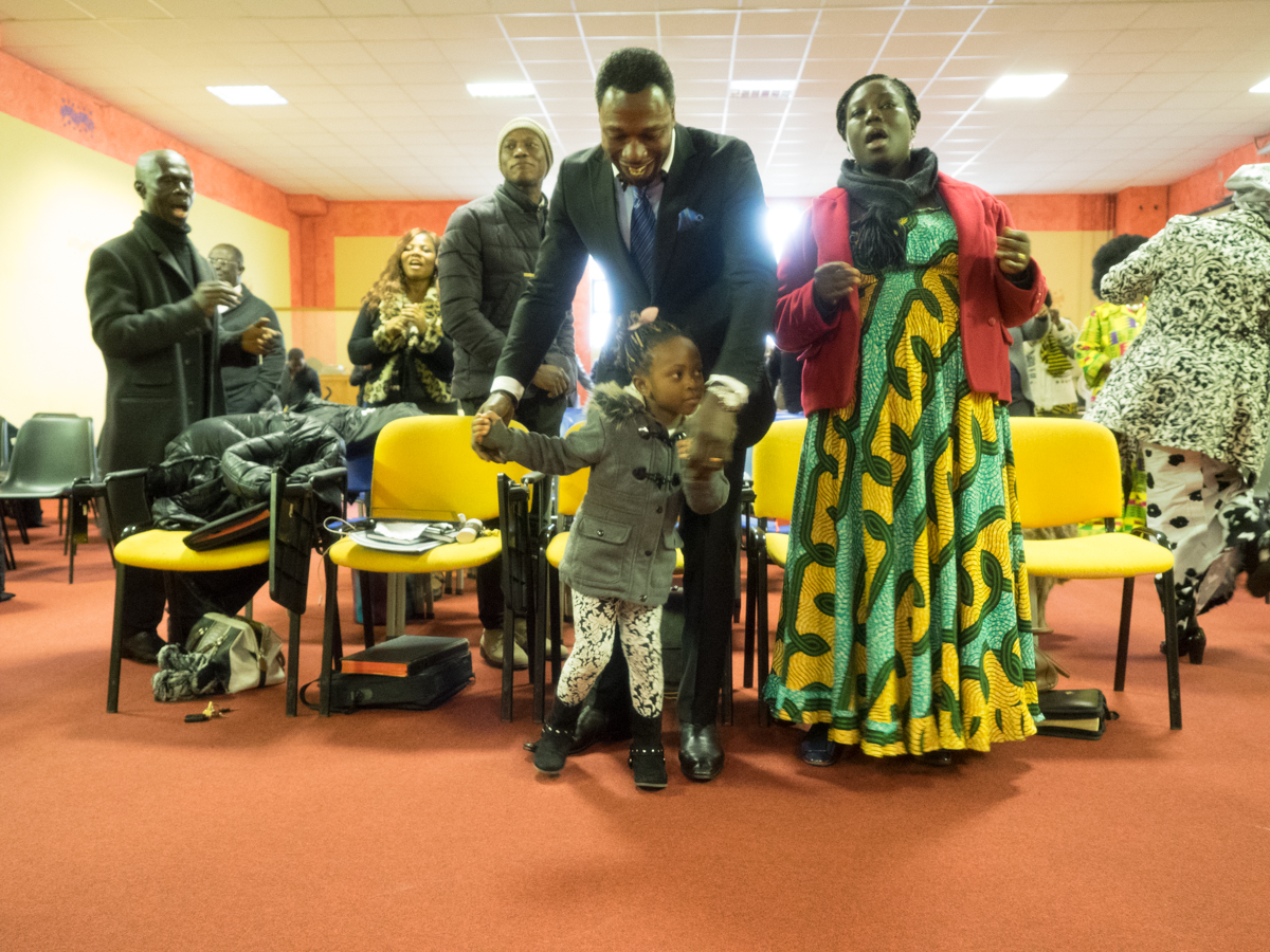 The pastor and his wife dance with a little girl